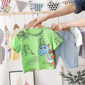 ست تی شرت و شورت بچه گانه طرح دایناسور رنگ سبز در دست فروشنده